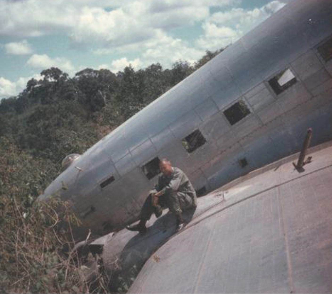 Roger sitting on a wing of a wrecked aircraft