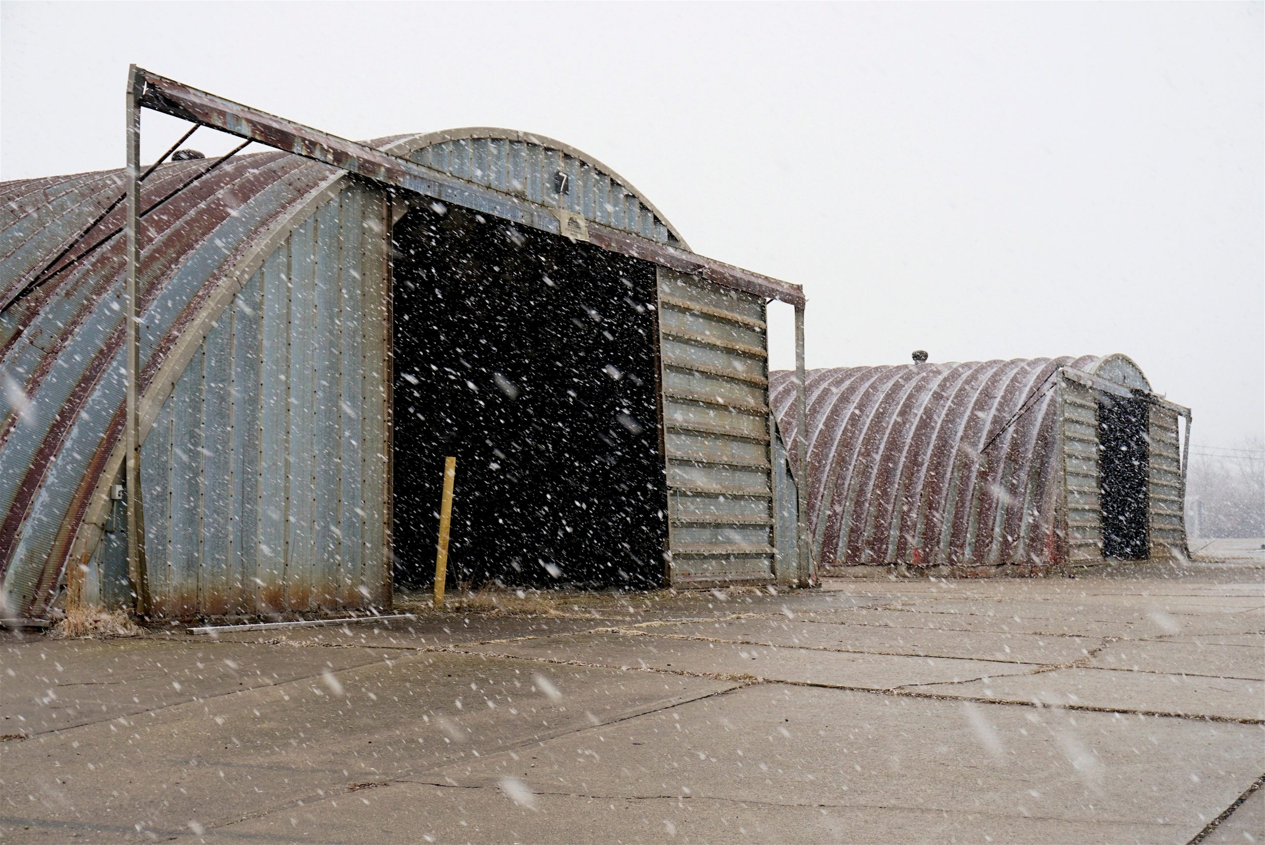 An old hanger with snow coming down